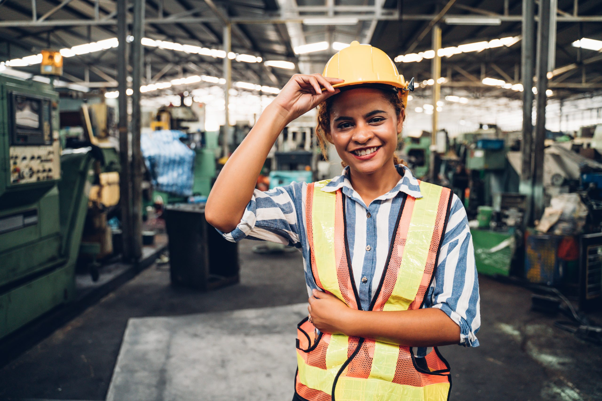 attractive young african woman smiling and working engineering in industry.Portrait of young female worker in the factory.Work at the Heavy Industry Manufacturing Facility concept.